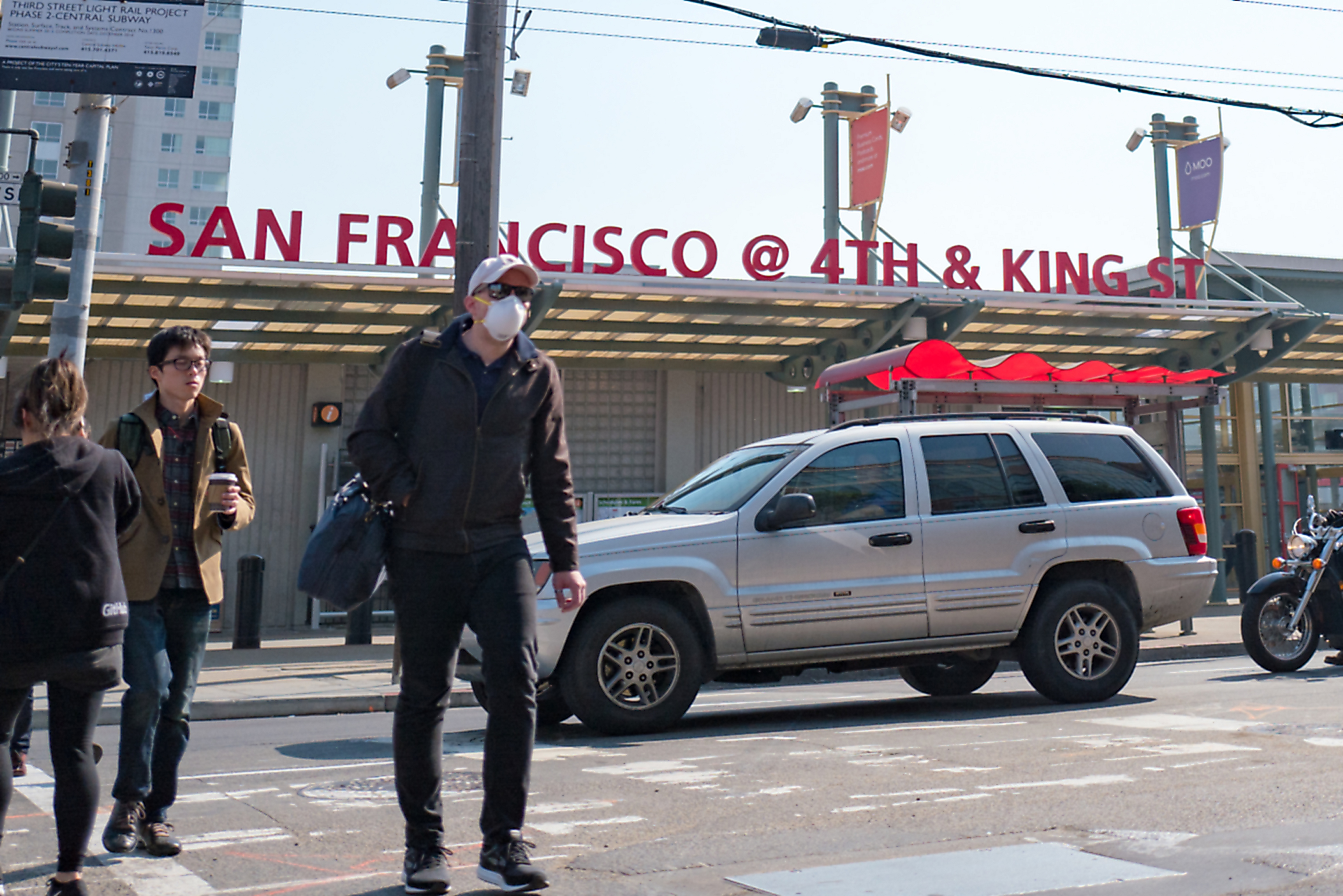A man wears a surgical face mask while crossing a street in the South of Market (SoMA) neighborhood of San Francisco, California, October 13, 2017.