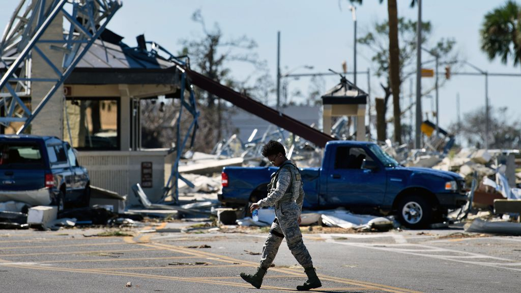 An officer walks near a destroyed gate in Tyndall Air Force Base in Florida, in the aftermath of Hurricane Michael.
