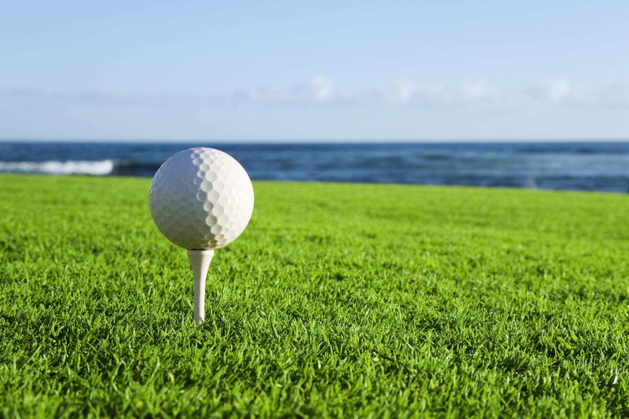 Golf ball on a tee by the ocean.