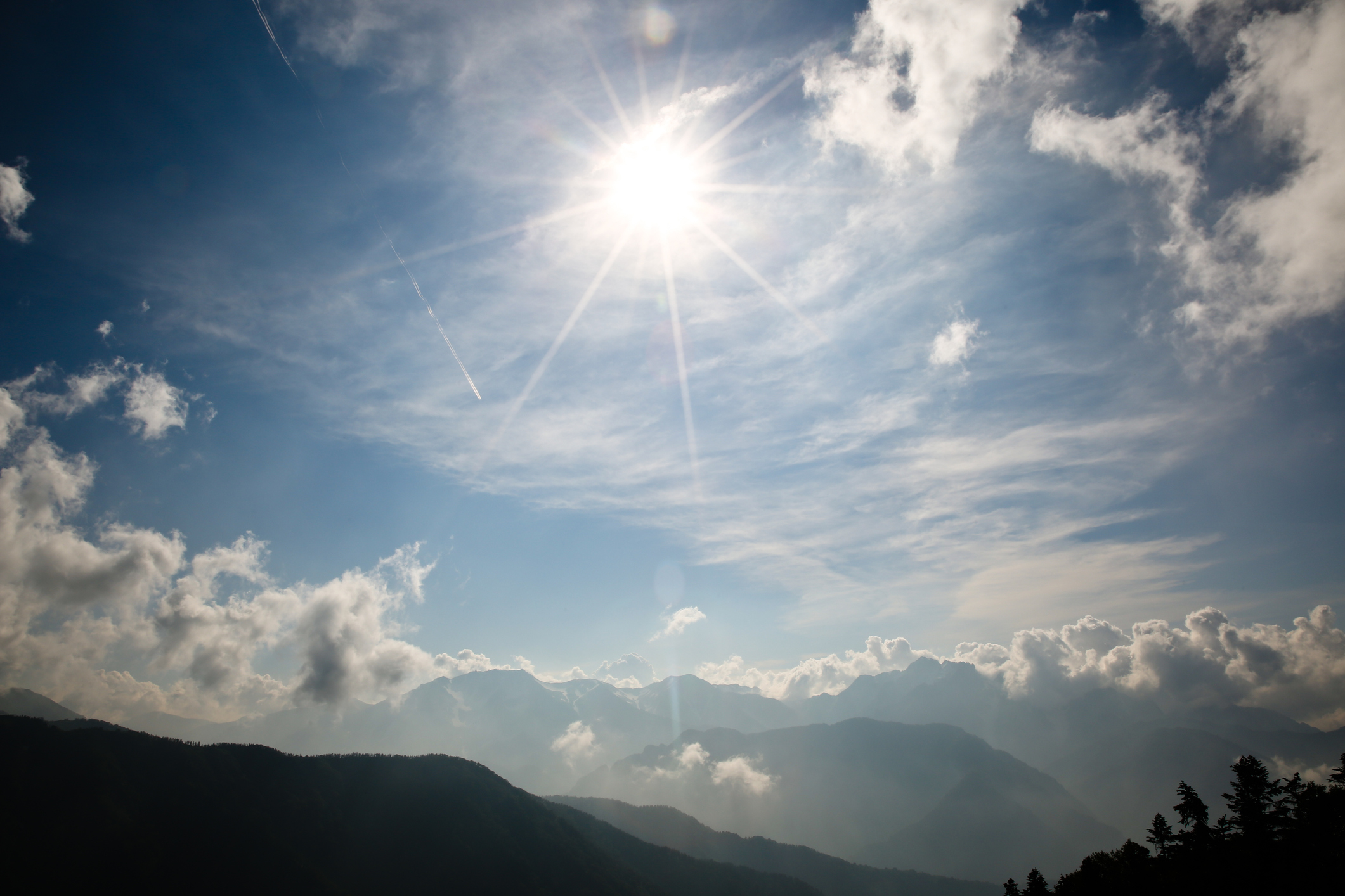 A view of the sun and clouds over mountains.