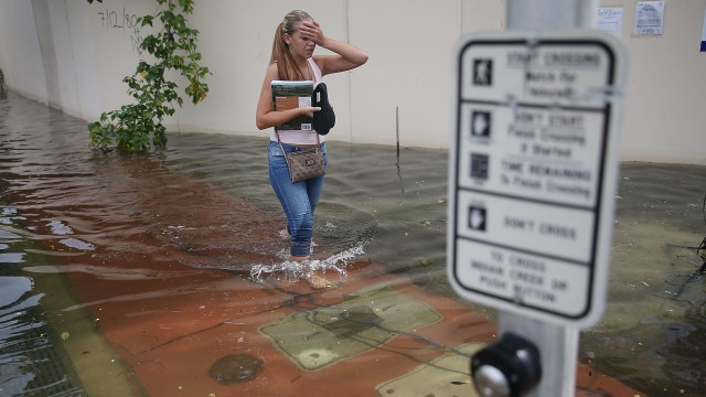 A woman walks through a flooded street in Miami Beach, Florida.