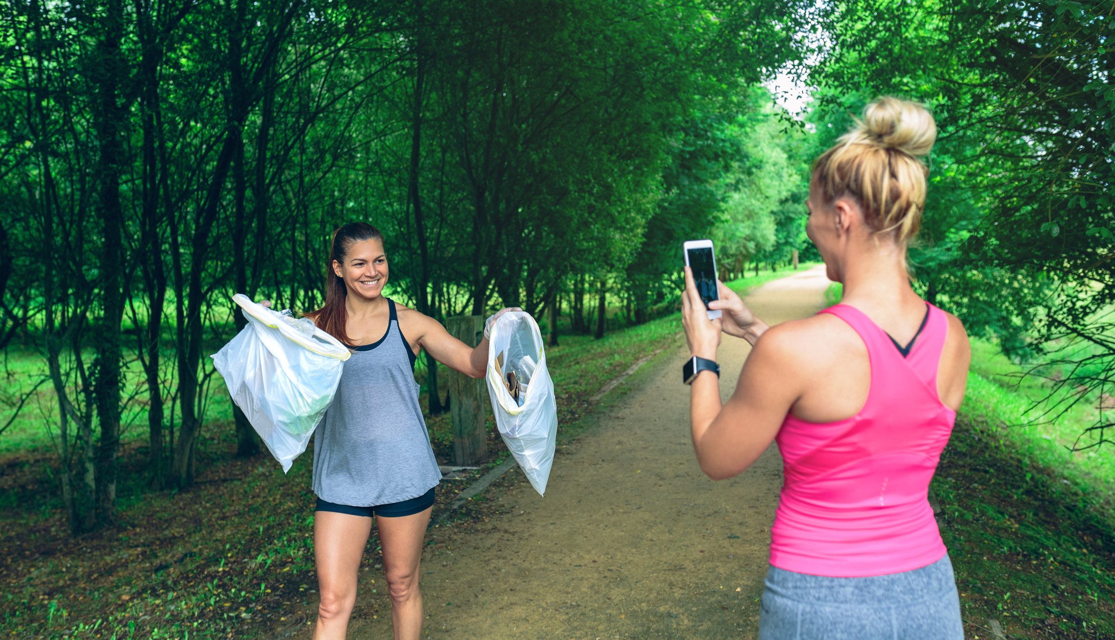 Girl taking a picture of a friend with trash bags after plogging