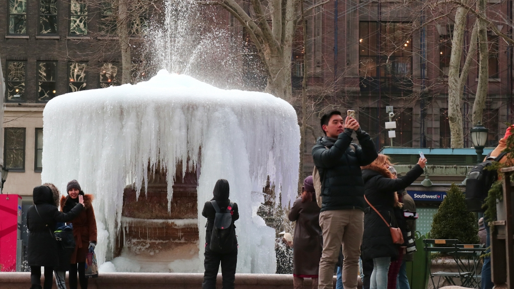People take selfies in front of frozen fountain in New York City.