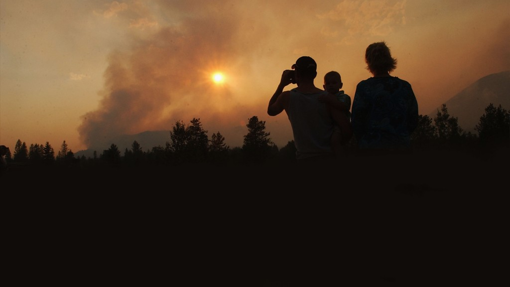 A family watches as smoke rises from the Robert Fire in Glacier National Park, Montana.