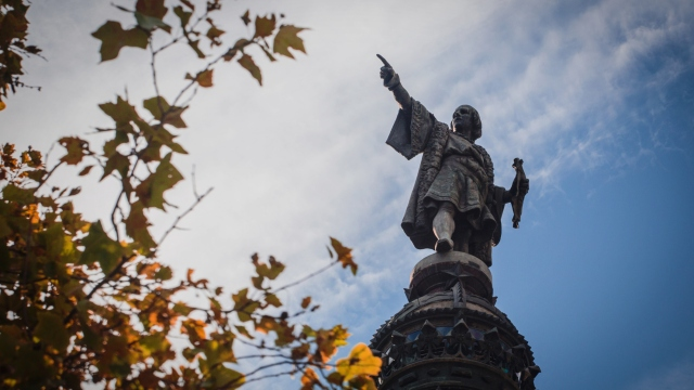 Monument of Christopher Columbus against a cloudy sky.