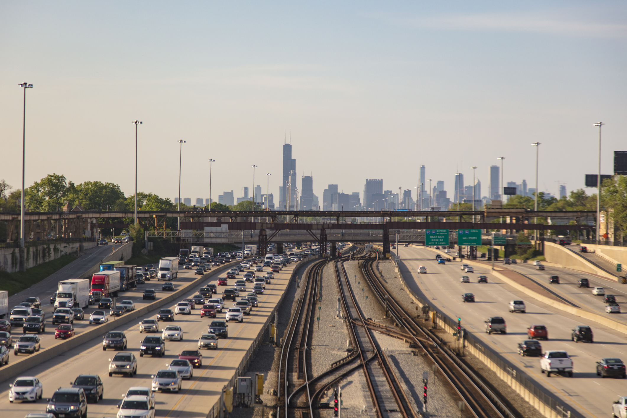 Elevated view of train tracks and multiple freeway lanes leading to Chicago. The skyline of Chicago covers the horizon. Moderate traffic leading into the city and heavy traffic leading away.
