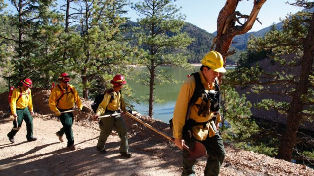 A fire crew hikes past McClure Reservoir in New Mexico en route to conducting a prescribed burn