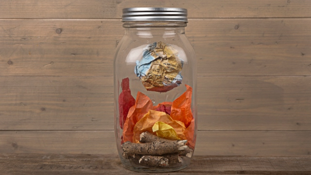 A creative and artistic representation of a paper fire in a jar with a crumpled world map and fire created from paper.
