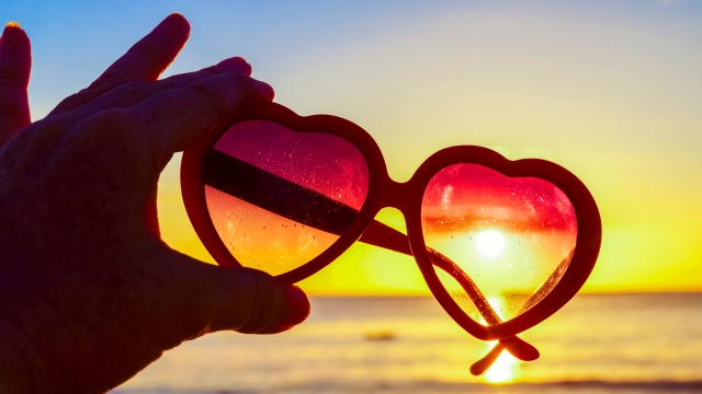 Hand holding heart-shaped sunglasses against the sun at beach, summer day