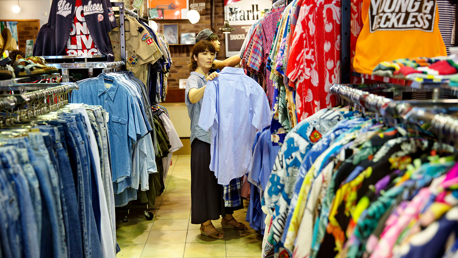 A women looks at second hand clothing at a second hand shop in Tokyo, Japan.