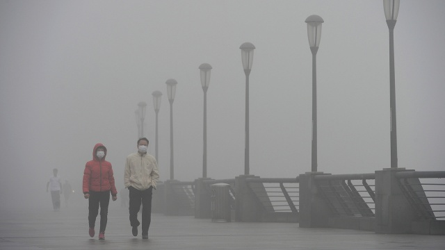 People wearing masks walk along The Bund on December 8, 2013 in Shanghai, China.