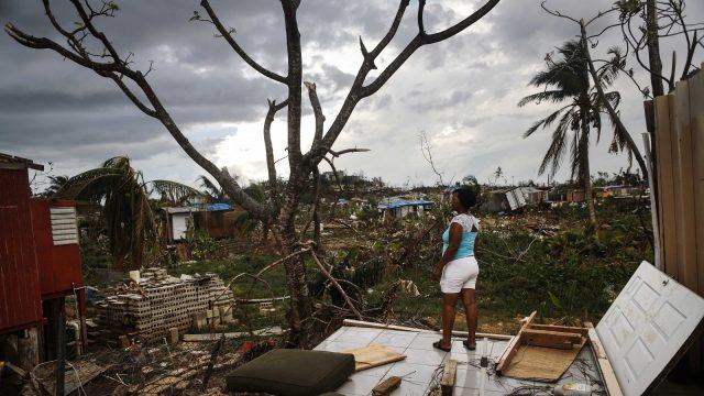 Woman looking at damage after Hurricane Maria.