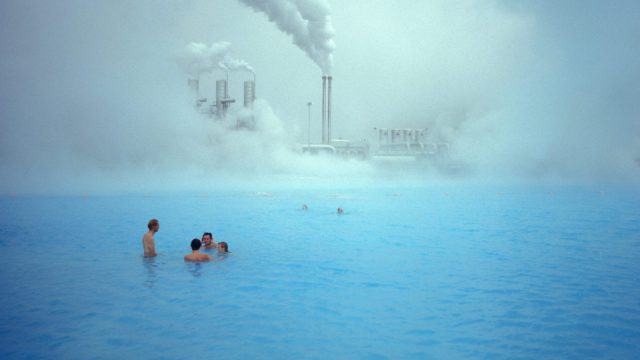 Icelandic bathers swim in front of a geothermal plant.