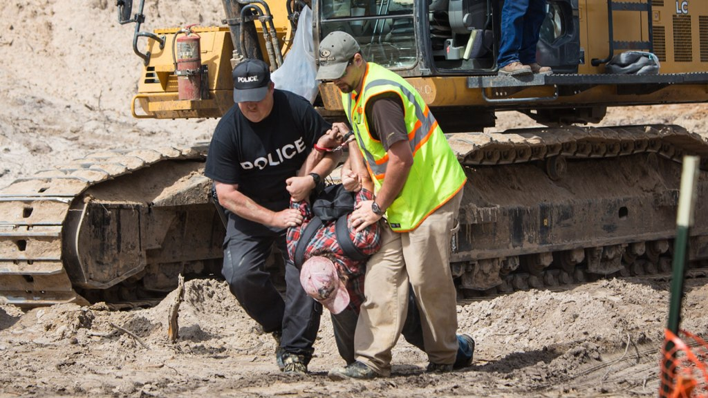 Environmental activist in the Tar Sands Blockade arrested after climbing on top of a work vehicle and attempting to attach a protest banner to it.