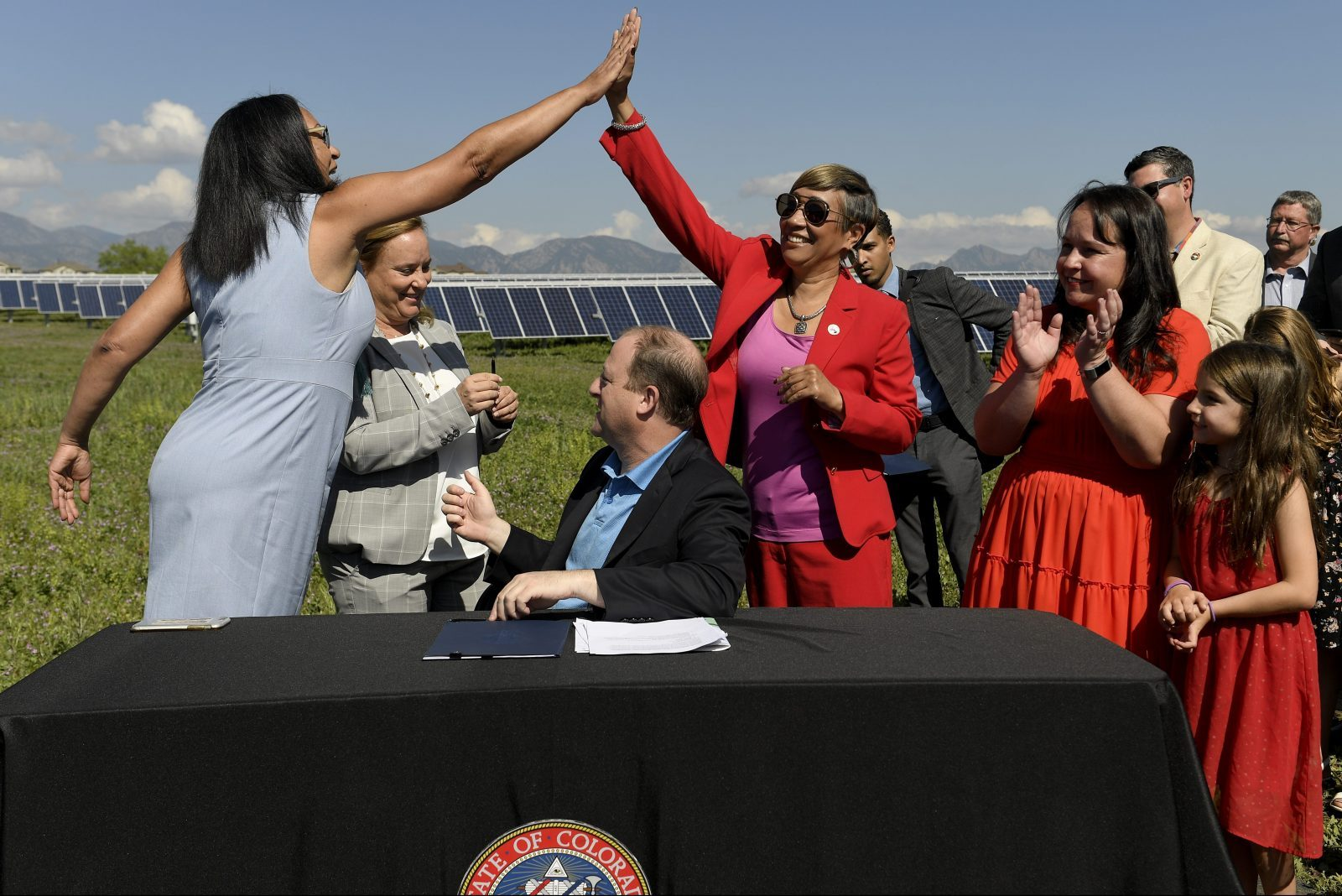 Representative Dominique Jackson and Senator Angela Williams High five after Governor of Colorado Jared Polis signs a climate action bill into law.