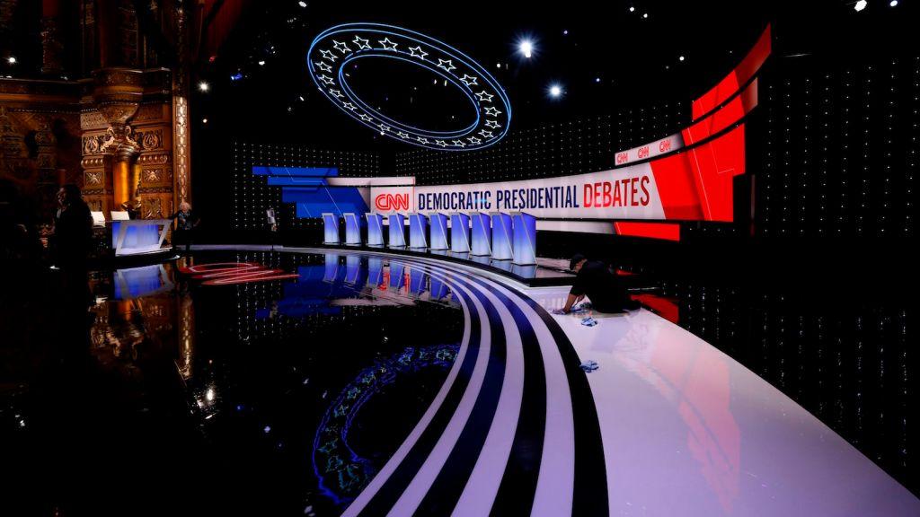 Workers prepare empty debate stage.