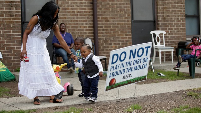 Camica Anderson, left, holds her son Logan Anderson's hand as other residents look on at the West Calumet Housing Complex on September 4, 2016 in East Chicago, Indiana.