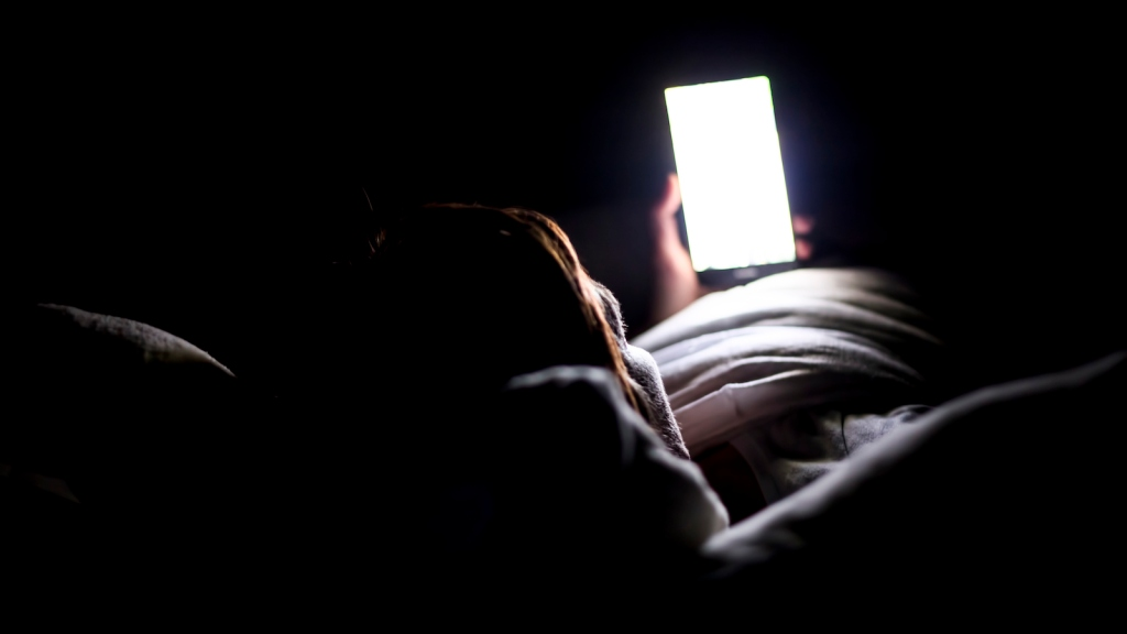 Woman looking up social medial at late night lying in bed, Internet addicted