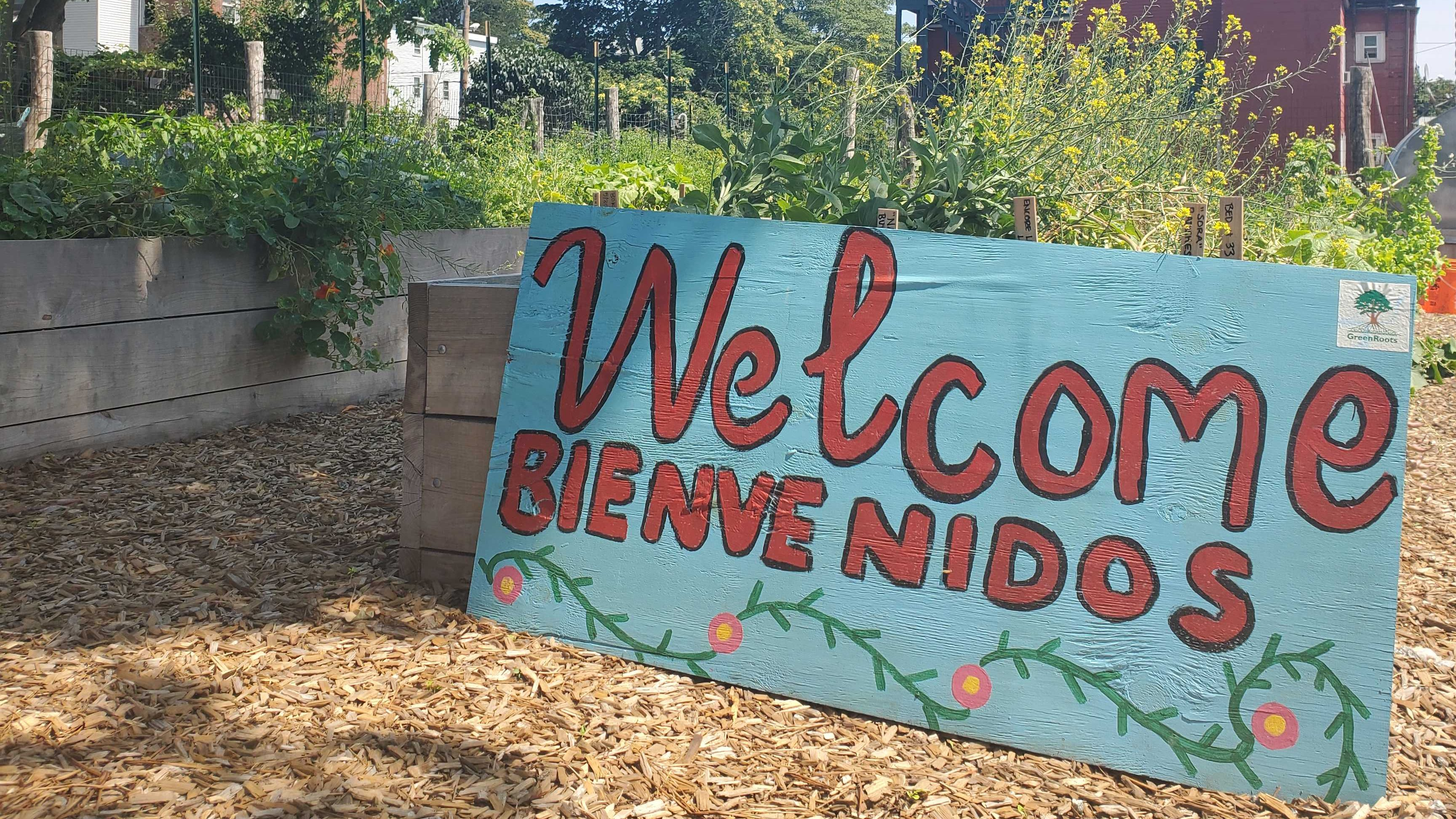 "A sign resting on a wooden garden bed overflowing with green plants reads ""Welcome, Bienvenidos."""