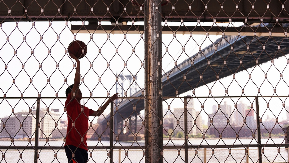 A teen plays basketball in the shade of a bridge along Manhattan's East River on August 27, 2014 in New York City.