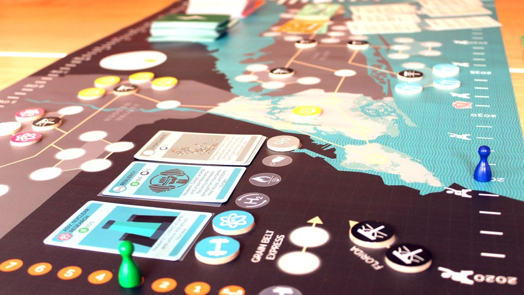 A photo of the board game Energetic showing playing cards and tokens on a map.