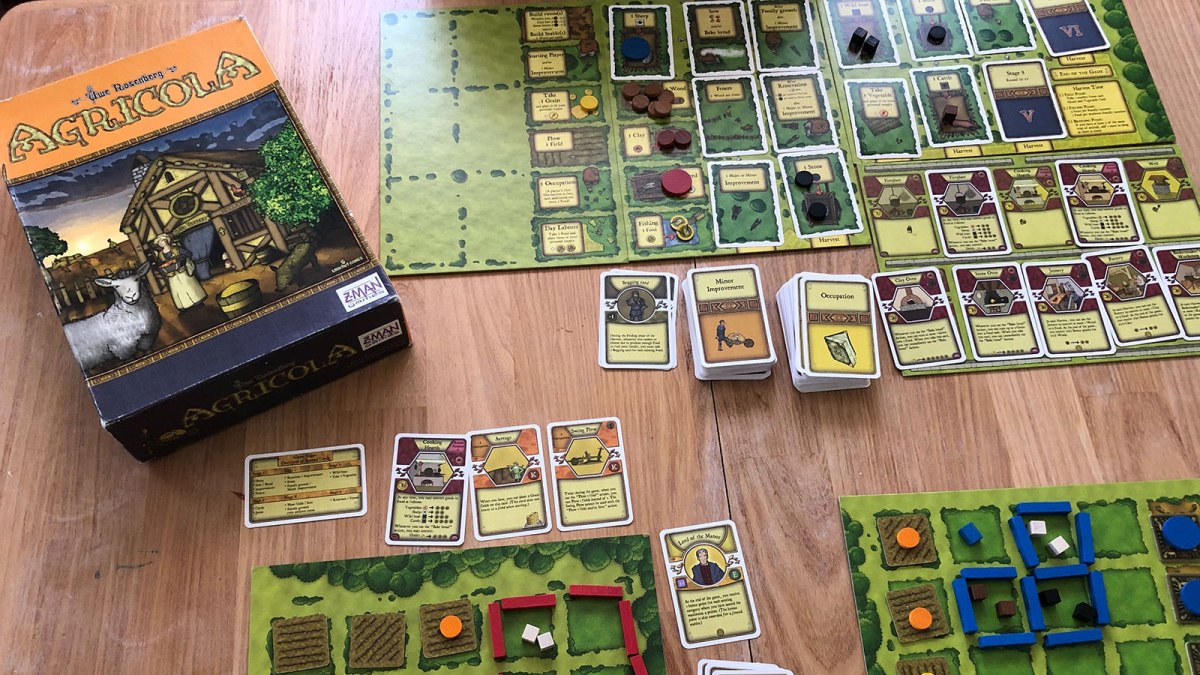 A photo of the game board for Agricola showing the box and playing cards.