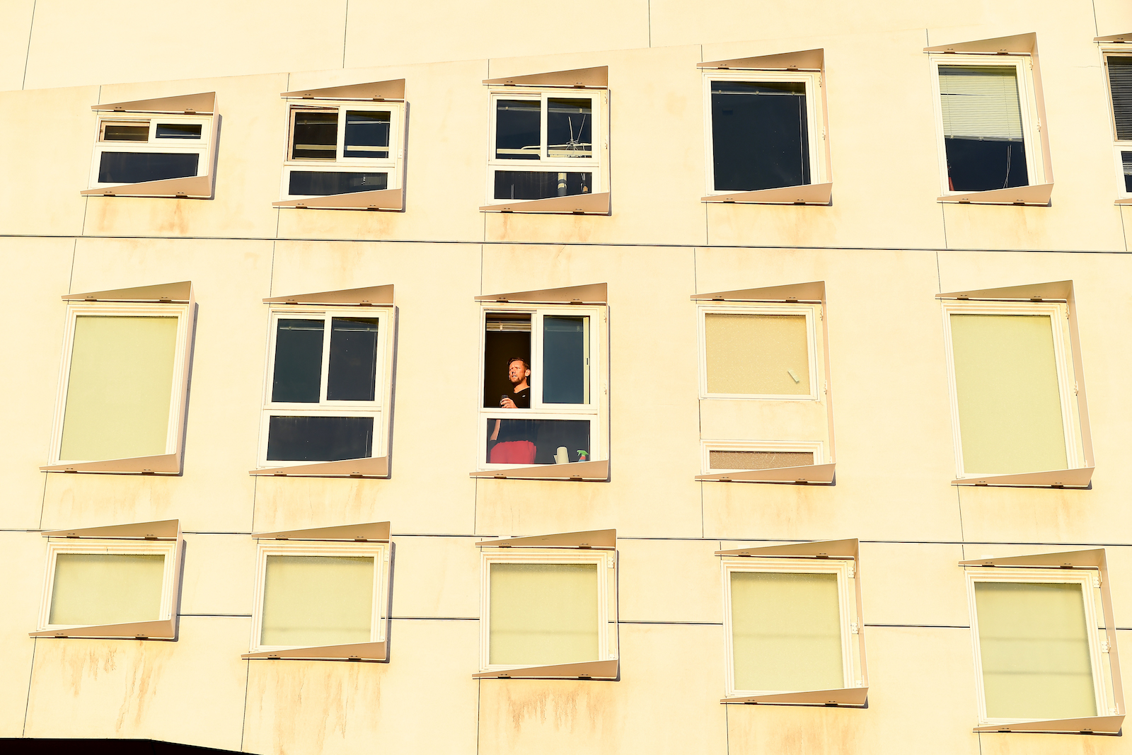 photo of man looking through apartment window during covid-19 pandemic