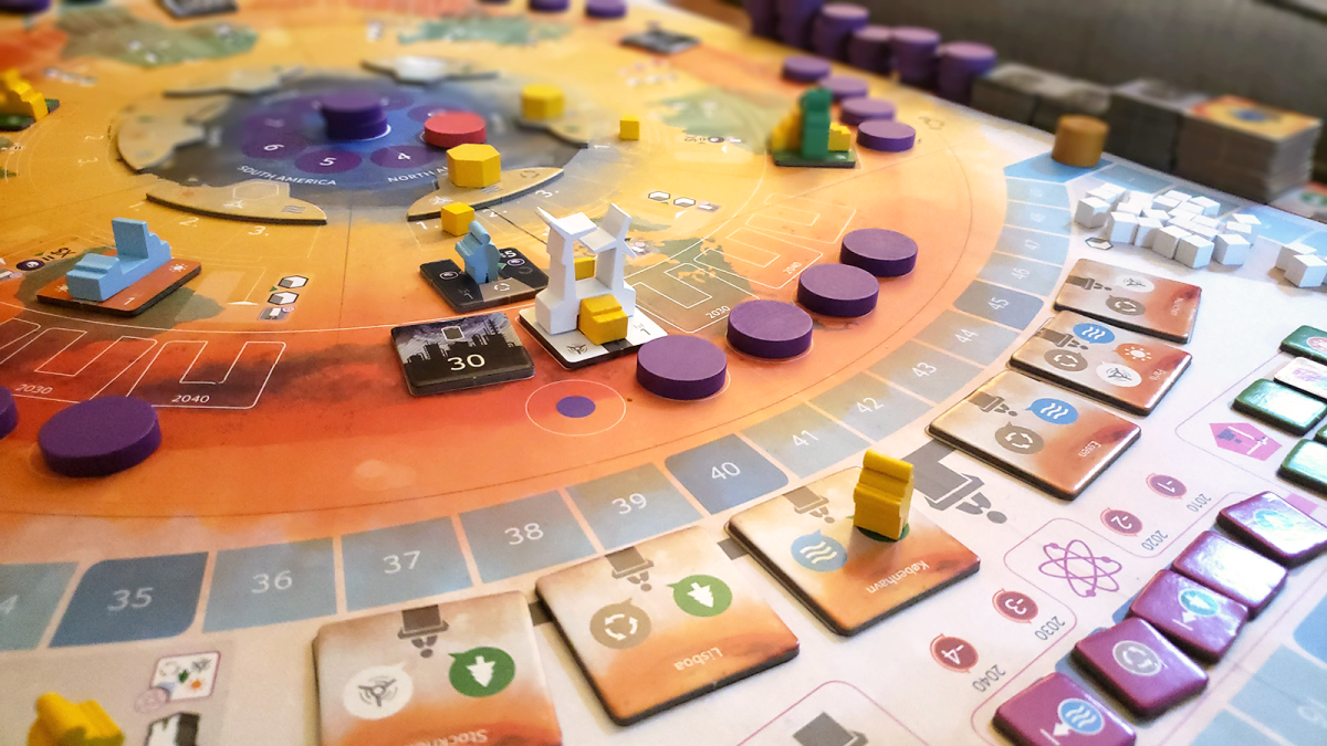 A photo of the game board for CO2: Second Chance. Various tokens and cards are scattered around a small wooden wind turbine.