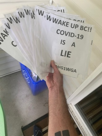 A photo of Walters holding COVID conspiracy signs above a recycling bin.