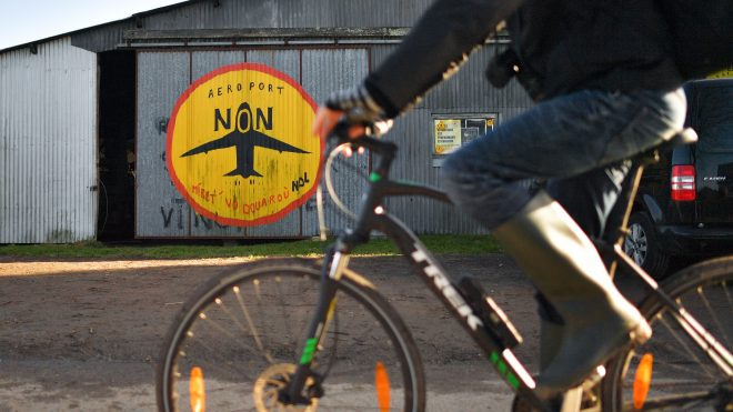 Photo of a person biking past a barn painted with an airplane, part of a utopian community protesting an airport in Western France.