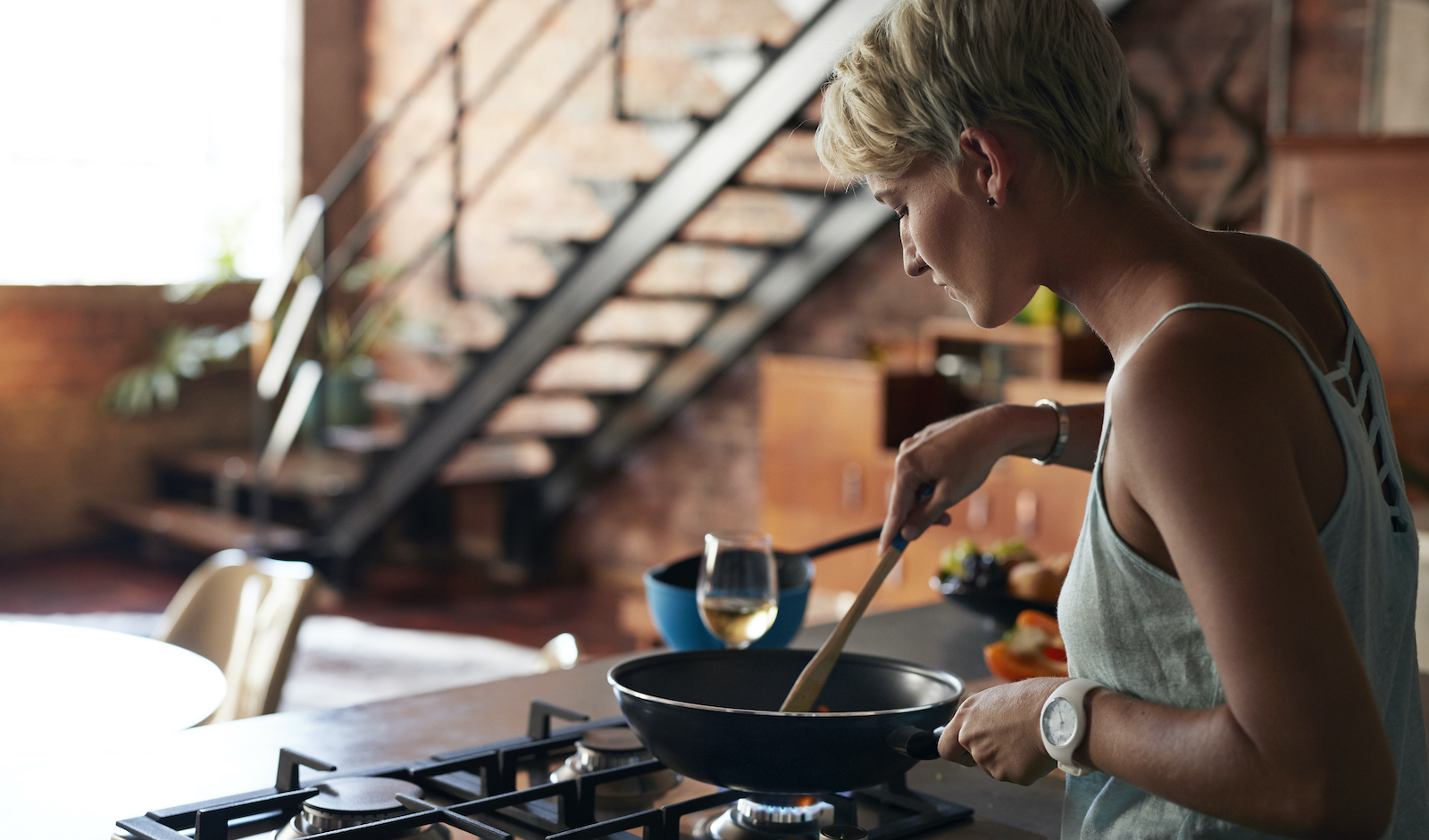 Woman cooking on gas stove.