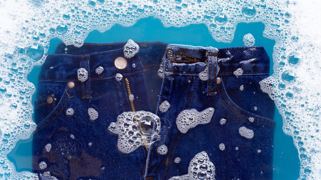 View of jeans being washed in water with soap bubbles