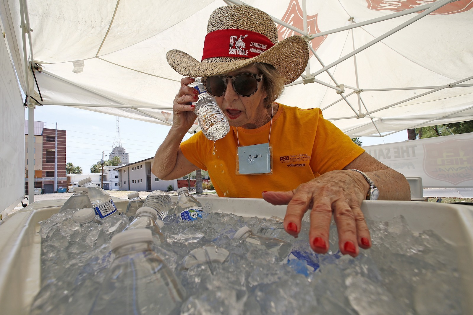 woman holds water bottle to her face during extreme heat wave