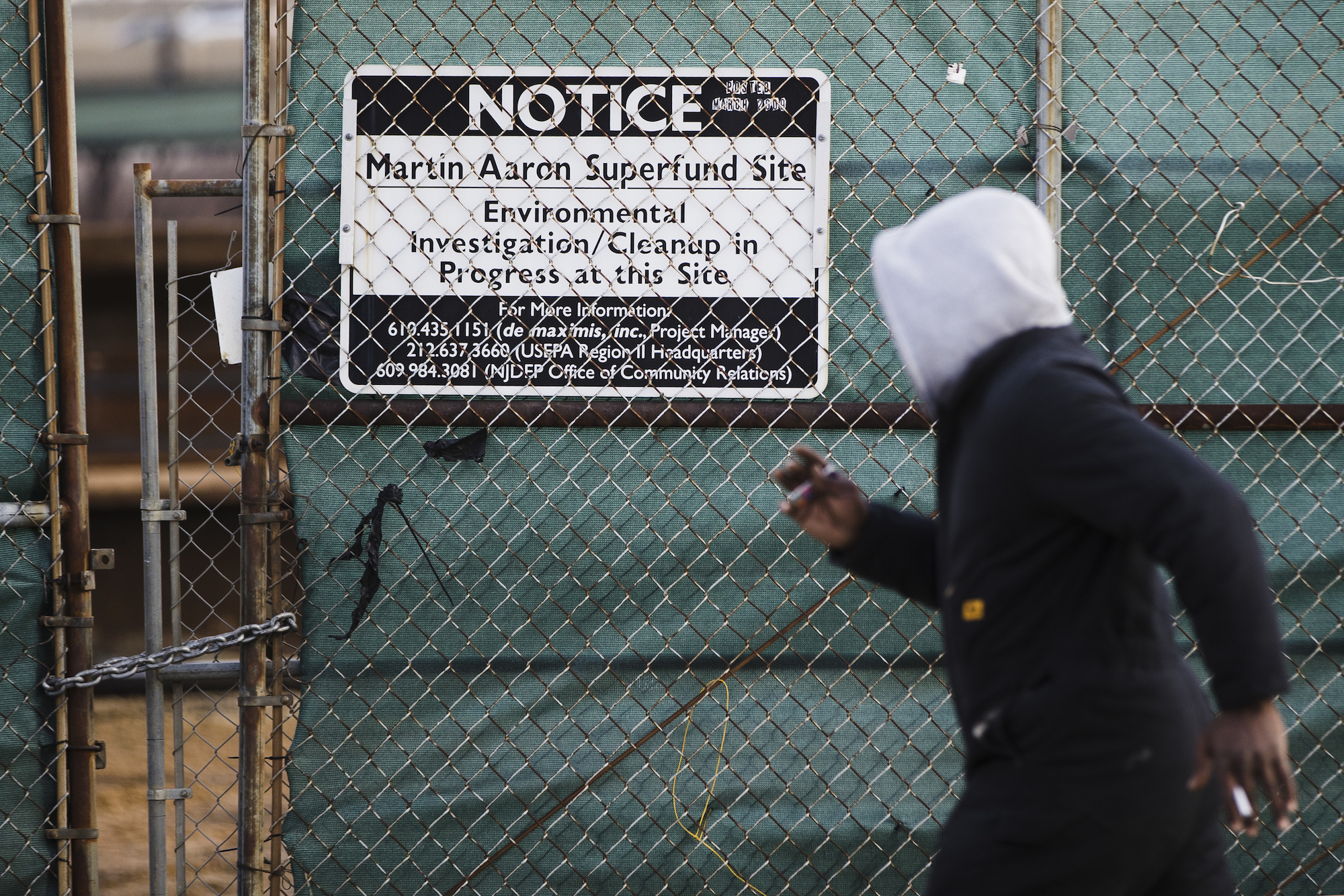 A photo of a man waking past a sign for the Martin Aaron Inc. Superfund site in Camden, New Jersey