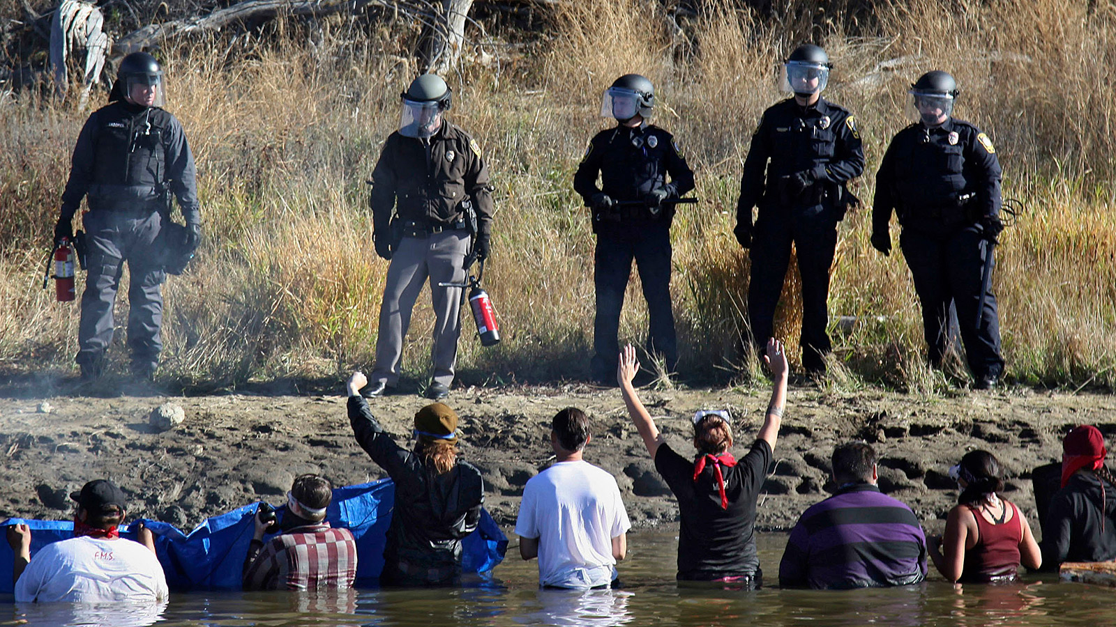 DAPL protestors wading in a creek confront police in riot gear