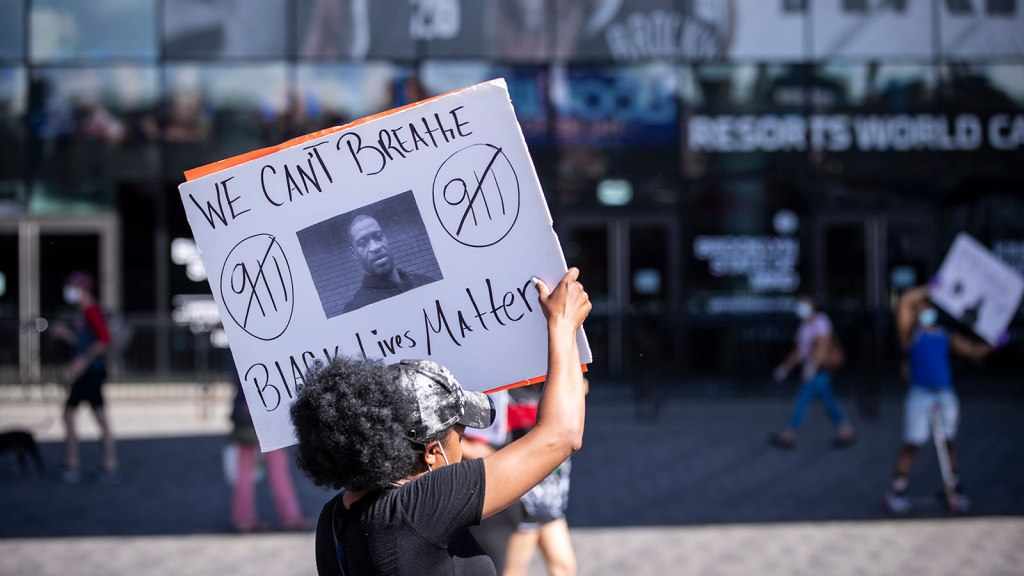 A protester wearing a mask around their neck holds a sign with a picture of George Floyd and saying We Cant Breathe and Black Lives Matter.
