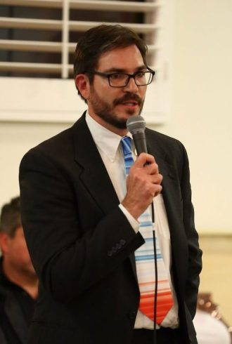 An image of Peter Kalmus holding a microphone and wearing a tie with blue, white, and red stripes