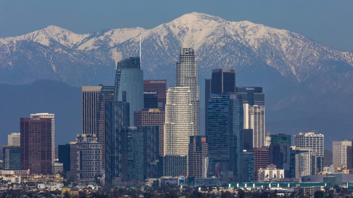 A photo of downtown Los Angeles buildings against backdrop of clear snow-capped mountains and blue skies