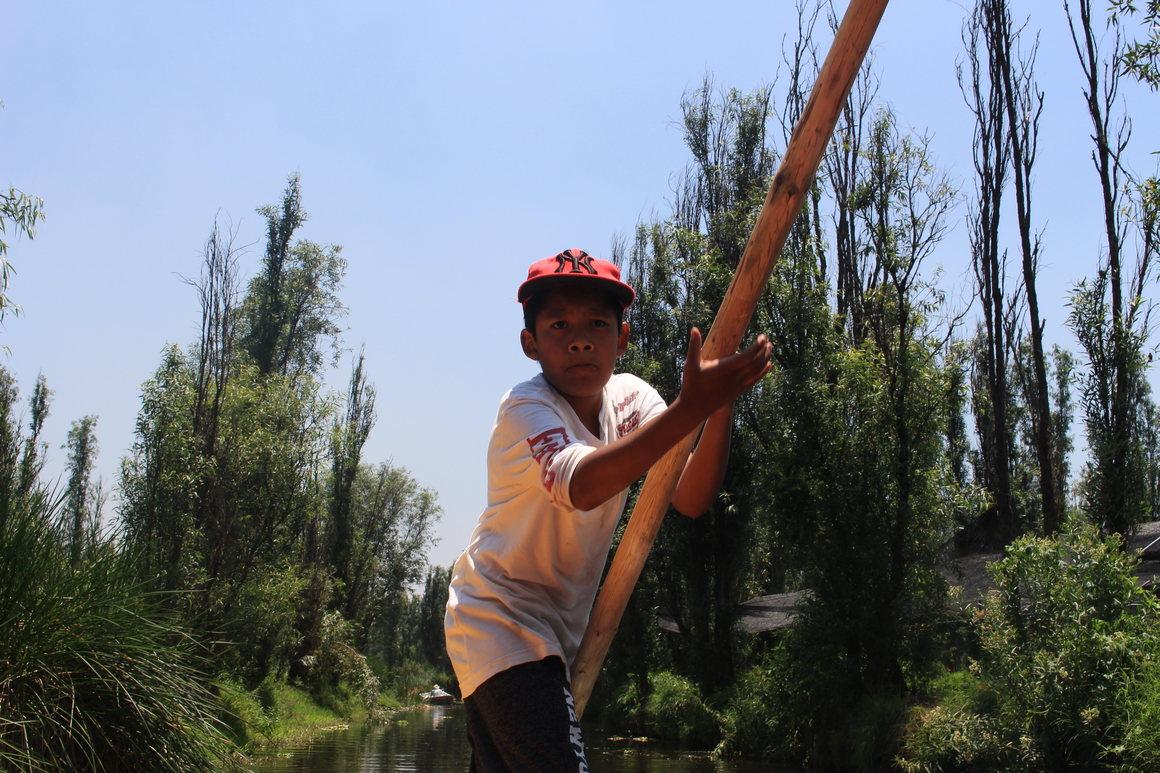 Axel navigates a trajinera on a canal in xochimilco
