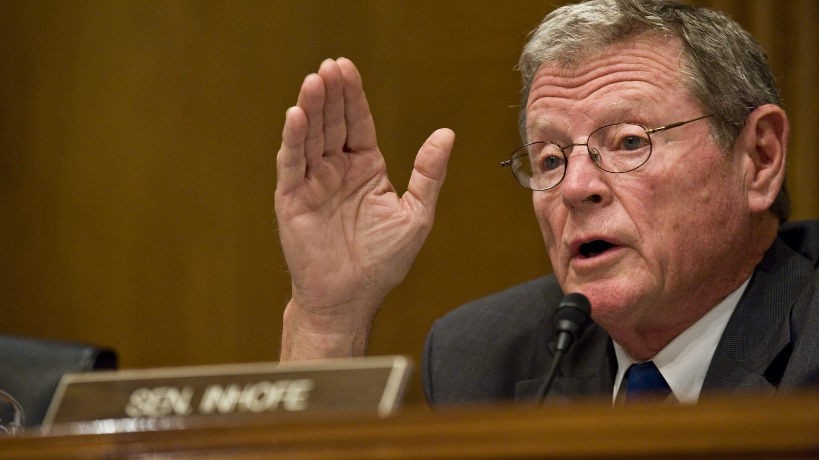 A photo fo James Inhofe with his hand in the air
