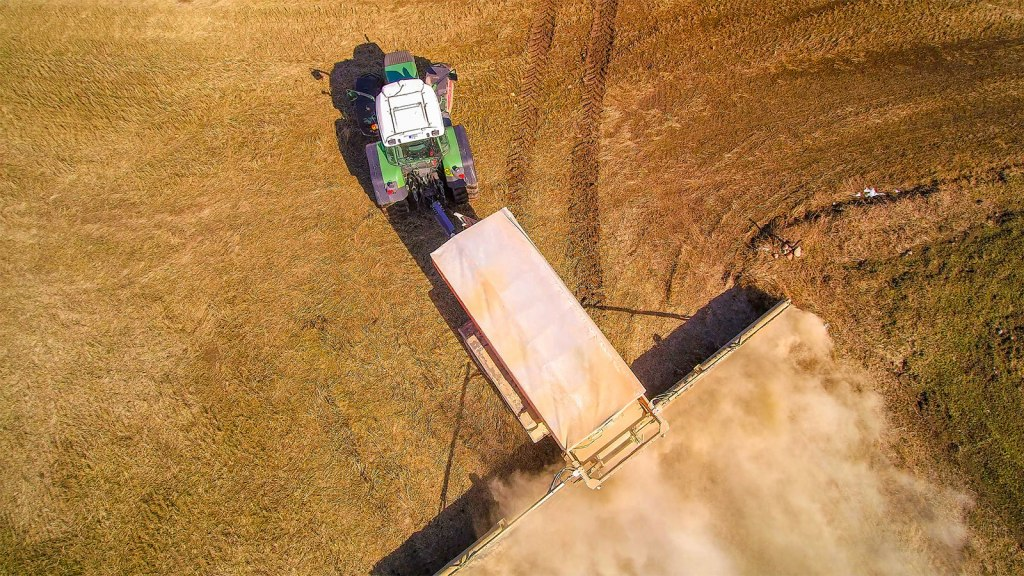 A green tractor spreading lime on a field