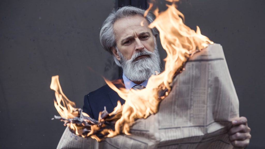 photo of man holding newspaper on fire