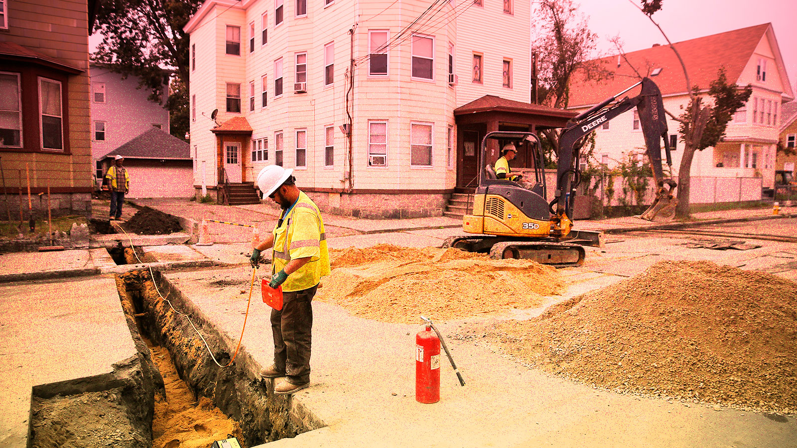 Photo of construction worker next to natural gas trench