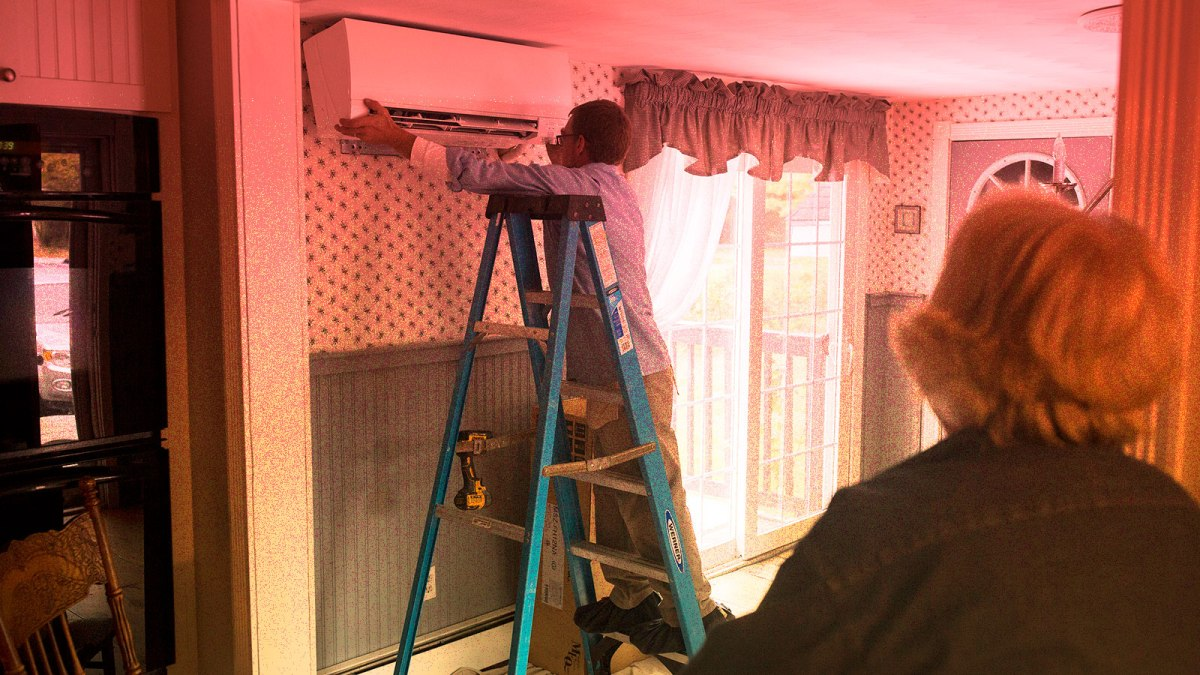 photo of woman watching heat pump being installed in her home