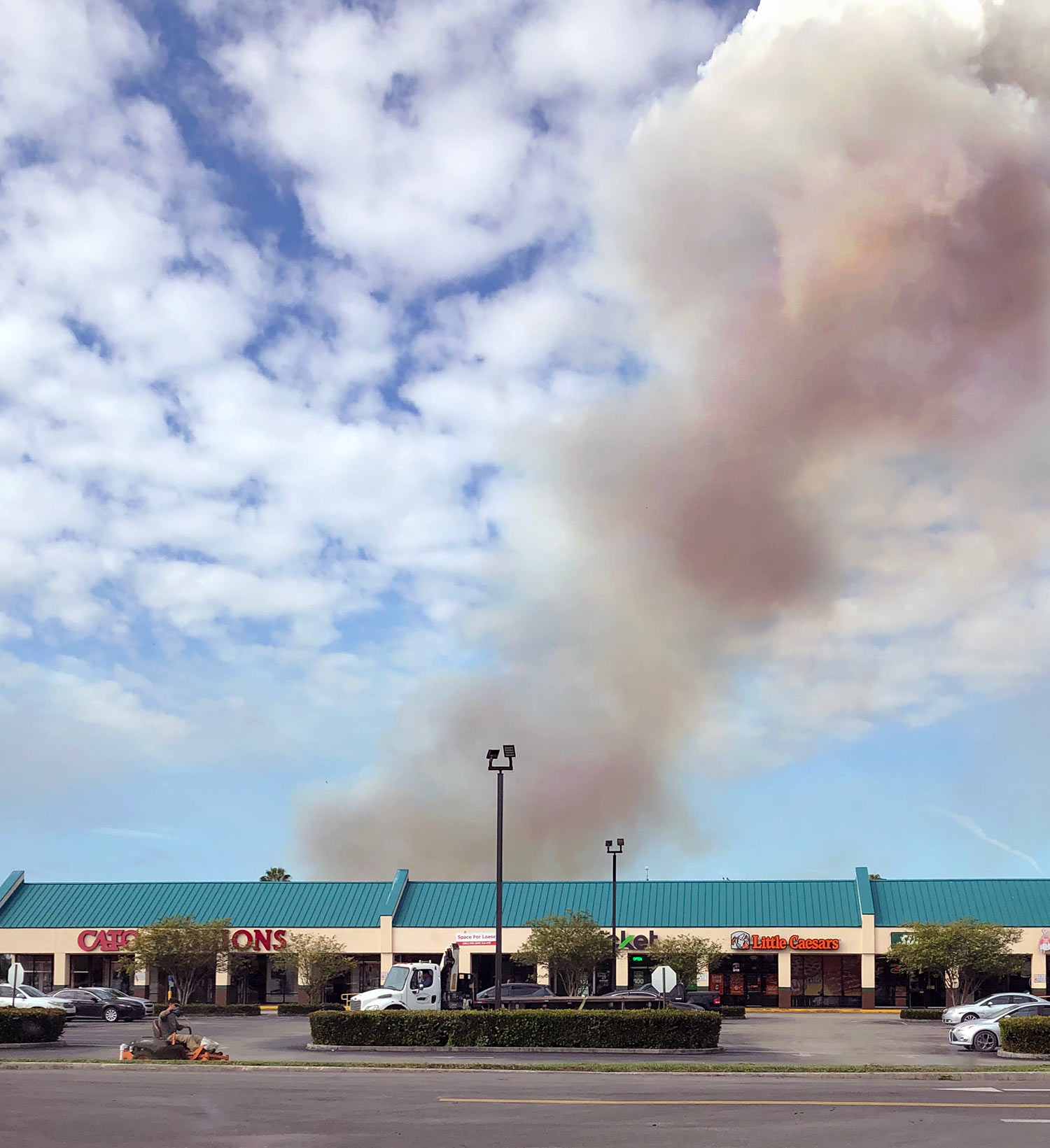 Smoke from a sugarcane burn appears over a strip mall in Belle Glade.