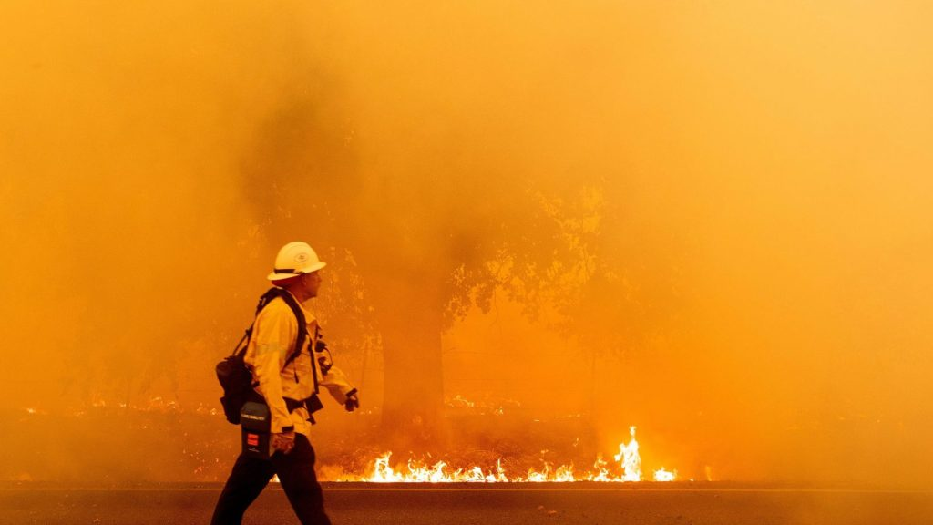 A Pacific Gas and Electric firefighter walks down a road as flames approach in Fairfield, California during the LNU Lightning Complex fire on August 19, 2020.