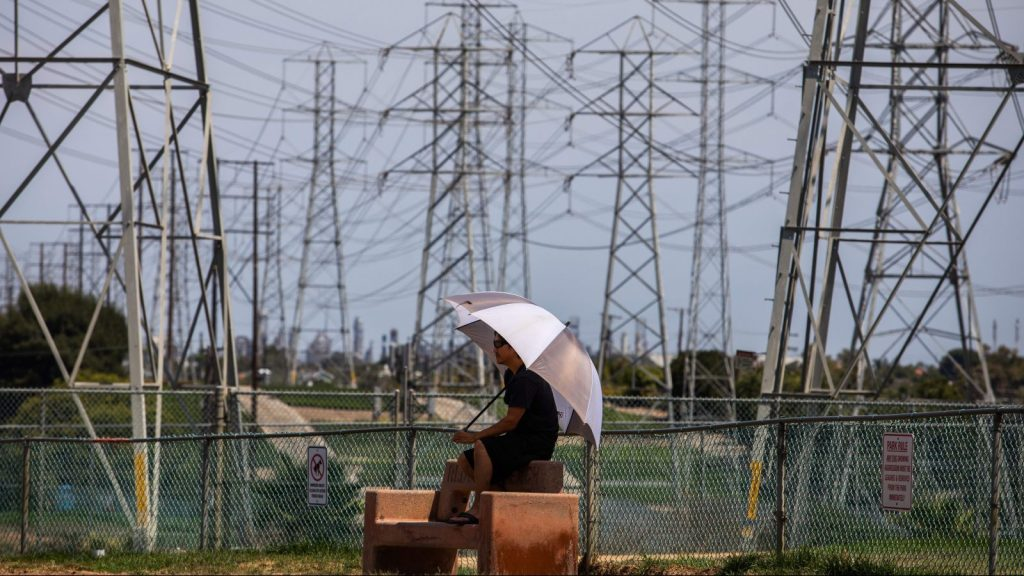 A man sits in the shade of his umbrella at the Dog Park under high tension power lines in Redondo Beach, California on August 16, 2020.
