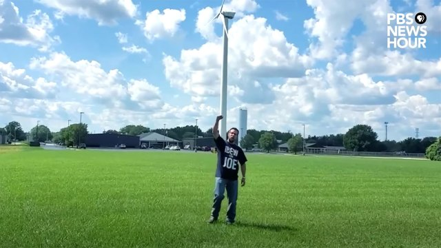 A man turns away from a large wind turbine and raises his fist in support of Joe Biden