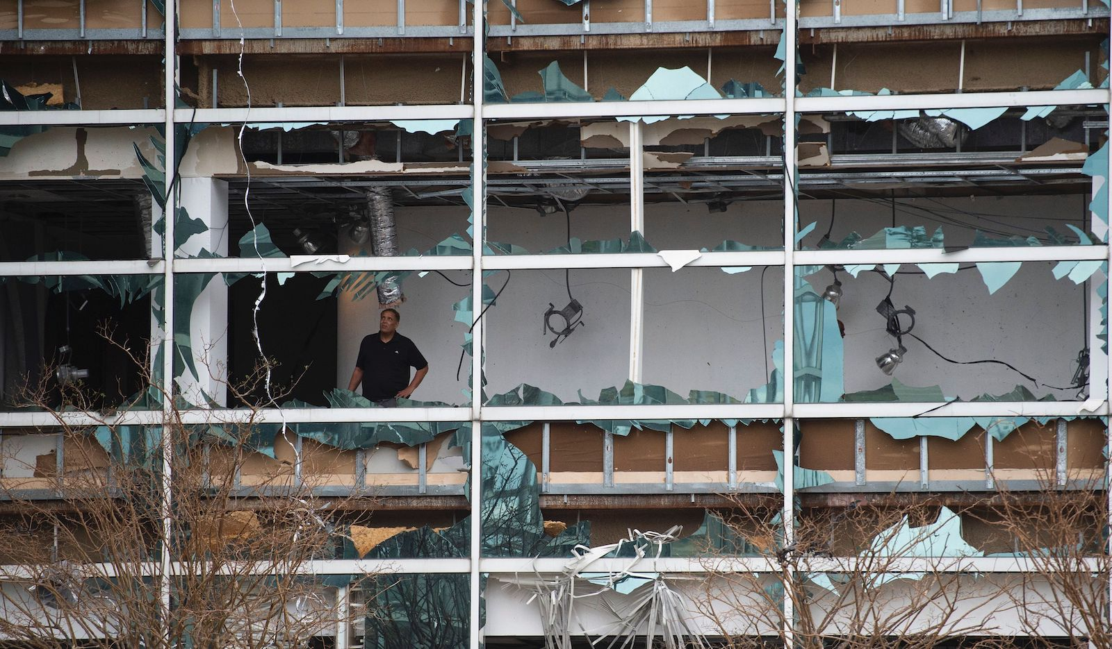A man looks at damage inside the Capitol One Bank Tower, with its windows blown out in the downtown area after Hurricane Laura passed through