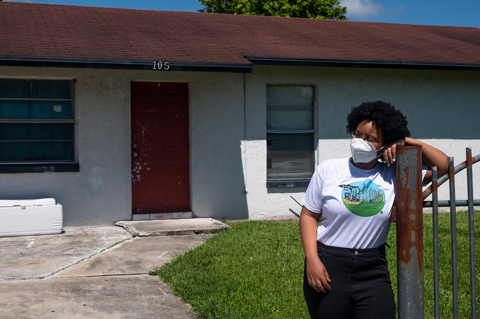 Kil'mari Phillips stands outside her home in South Bay, Florida — a few hundred feet away from Rosenwald Elementary School and the acres of sugarcane adjacent to it.